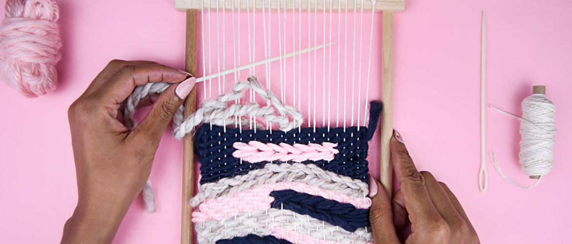 two hands weaving a small wall hanging