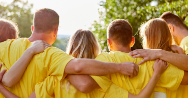 team wearing yellow tshirts with arms around each other
