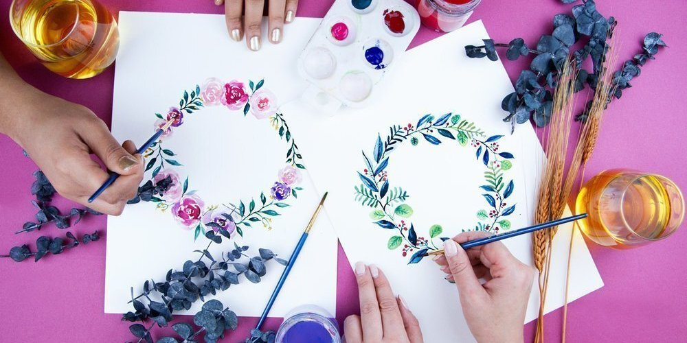 Hands creating watercolor floral wreaths