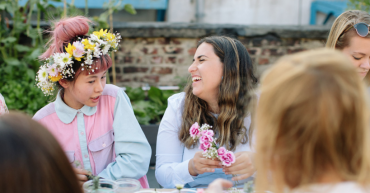 women laughing and making flower crowns